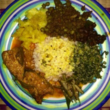 Clockwise from top: keema (ground beef) with peas, green spinach, green beans, fish curry, cabbage all served around a bed of red rice