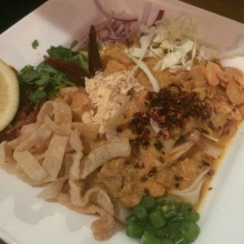 Bun Tay Kauswer (coconut chicken curry flour noodle, not available vegetarian) flour noodles with a stronger coconut curry sauce, split yellow pea, eggs, cabbage, and fried onions
