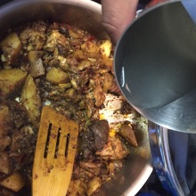 adding coconut water to the Kerala chicken (thighs) curry